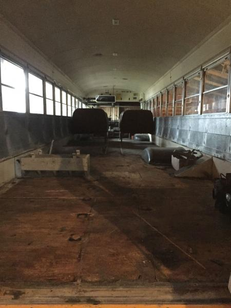 Seats and first layer of floor removed in back half of the bus.