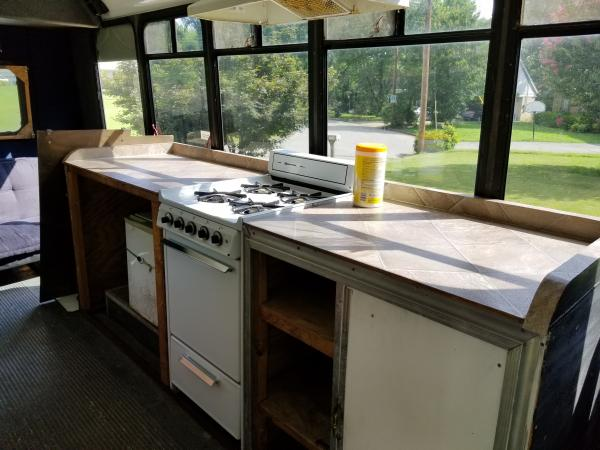 1. This is how it came. View from front of driver's side. Counter with shelves under, propane stove (top works, bottom doesn't), and really small under-counter refrigerator. Everything is going.